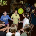 Camp Illahee counselors holding hands during orientation, keeping a yellow balloon in the air.