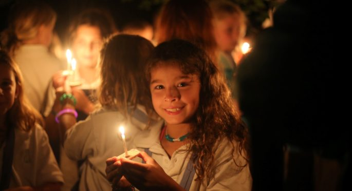 A Camper Holds a Wish Boat candle on the last night of camp.