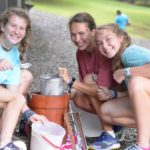 Two campers make homemade ice cream with their counselor.