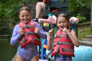 Two Illahee campers in bathing suits and life jackets give the thumbs up before jumping in the water.